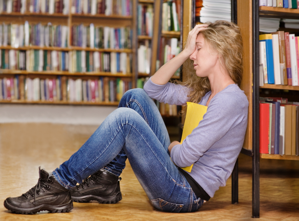 Upset girl in library sitting against bookshelf with head in hand