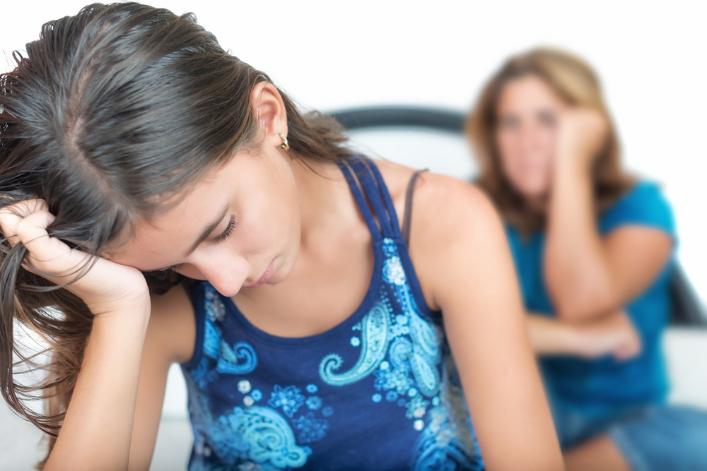 Teen girl with head in hand with upset mother behind her