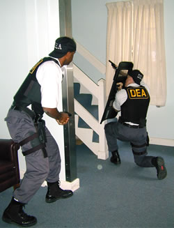 DEA agents with gun and shield checking out a house