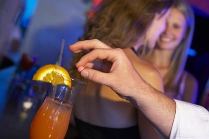 A man drops a pill into someone's drink at a bar