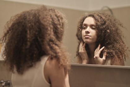 teen girl looking into mirror