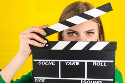 teen holding movie clapper