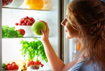 teen looking at vegetables in fridge