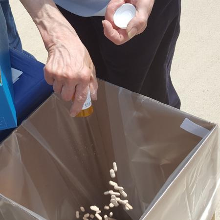 man disposing of pills during Take Back Day