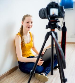 teen girl vlogging with laptop and video camera