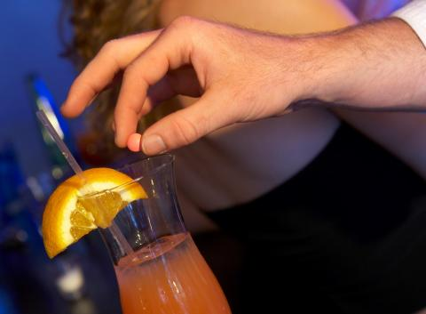 man putting date rape drug into a drink