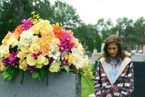 Girl standing by headstone with flowers