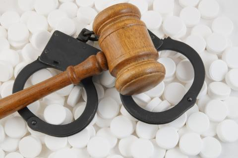 Handcuffs with judge's gavel over a pile of white pills