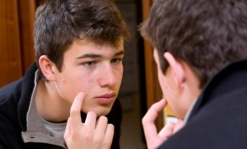 teen boy looking at acne in mirror