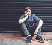 sad teen boy sitting on pavement